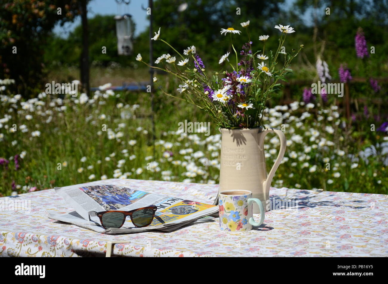 c1acc0889a66e Coffee or tea break in a sunny back garden table with the Sunday papers and  wildflowers