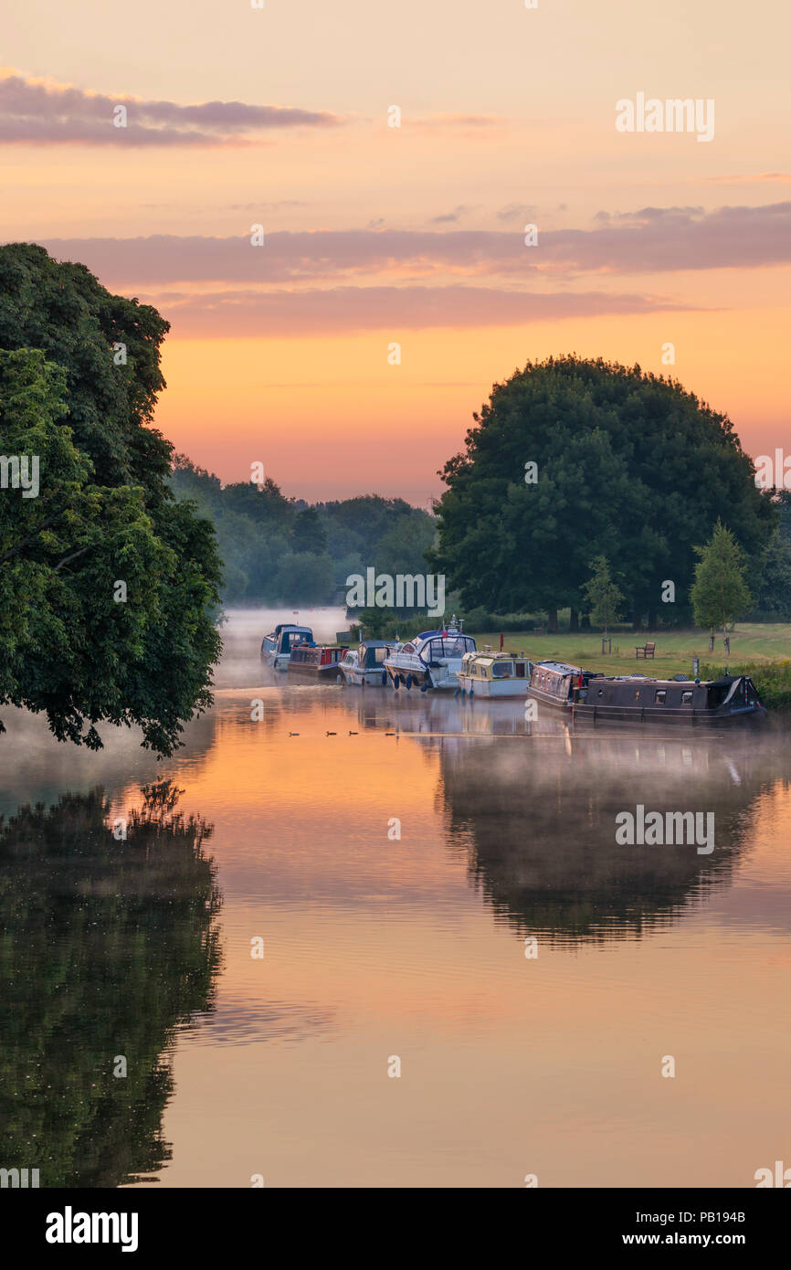 Boats moored on riverbank of the River Thames in dawn mist, Abingdon-on-Thames, Oxfordshire, England, United Kingdom, Europe - Stock Image