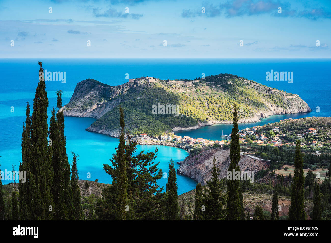 View to Assos village in sun light and beautiful blue sea. Cypress trees in foreground. Kefalonia island, Greece - Stock Image