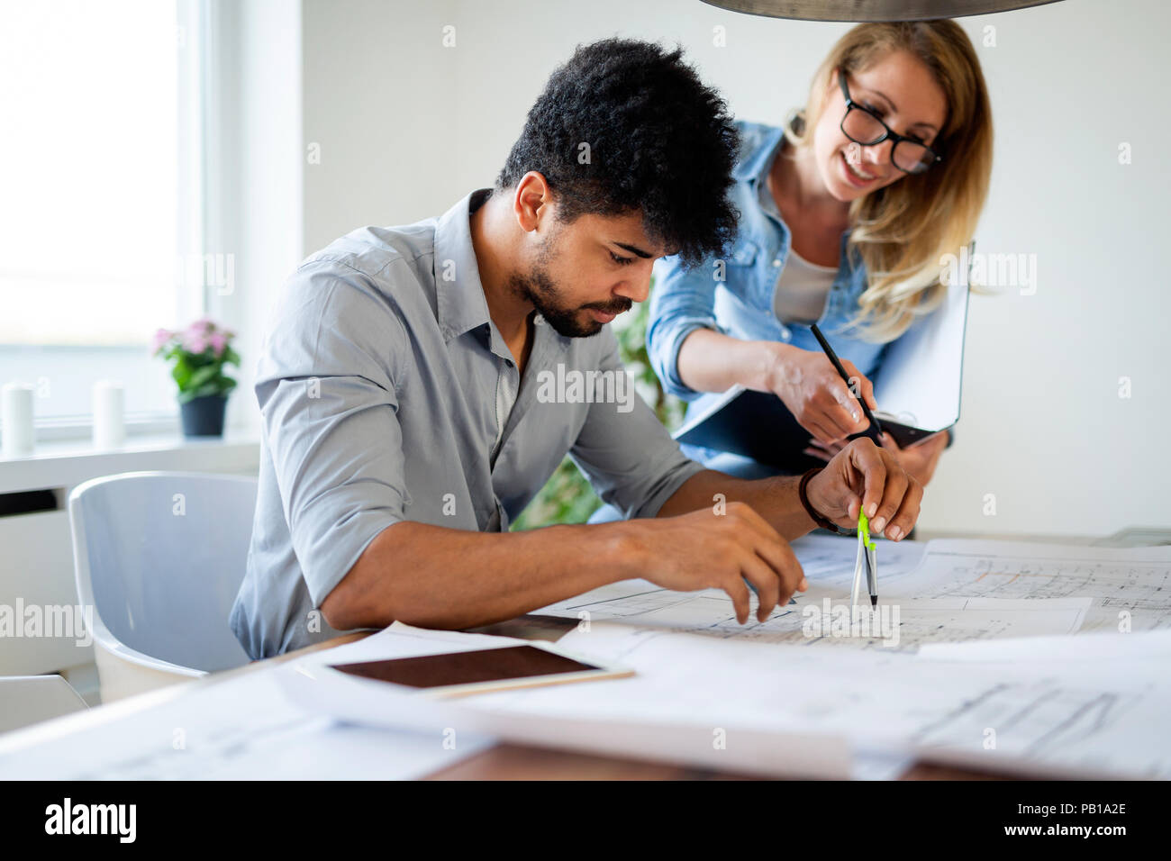 Office coworkers in business meeting discussing project plans - Stock Image