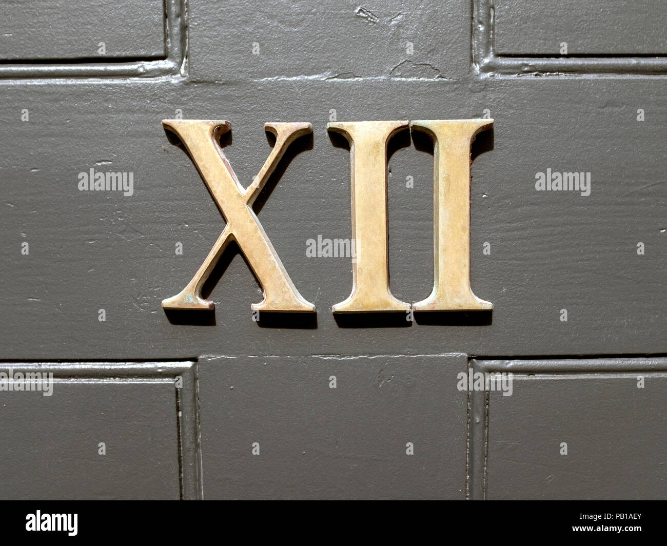 Number 12 in Roman numerals on a door in Edinburgh, Scotland, United Kingdom. - Stock Image