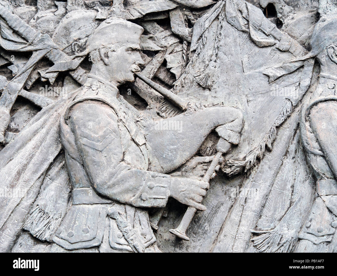 A detail of the Scottish American Memorial in Princes Street Gardens, Edinburgh, Scotland, United Kingdom, showing a kilted bag piper. Stock Photo