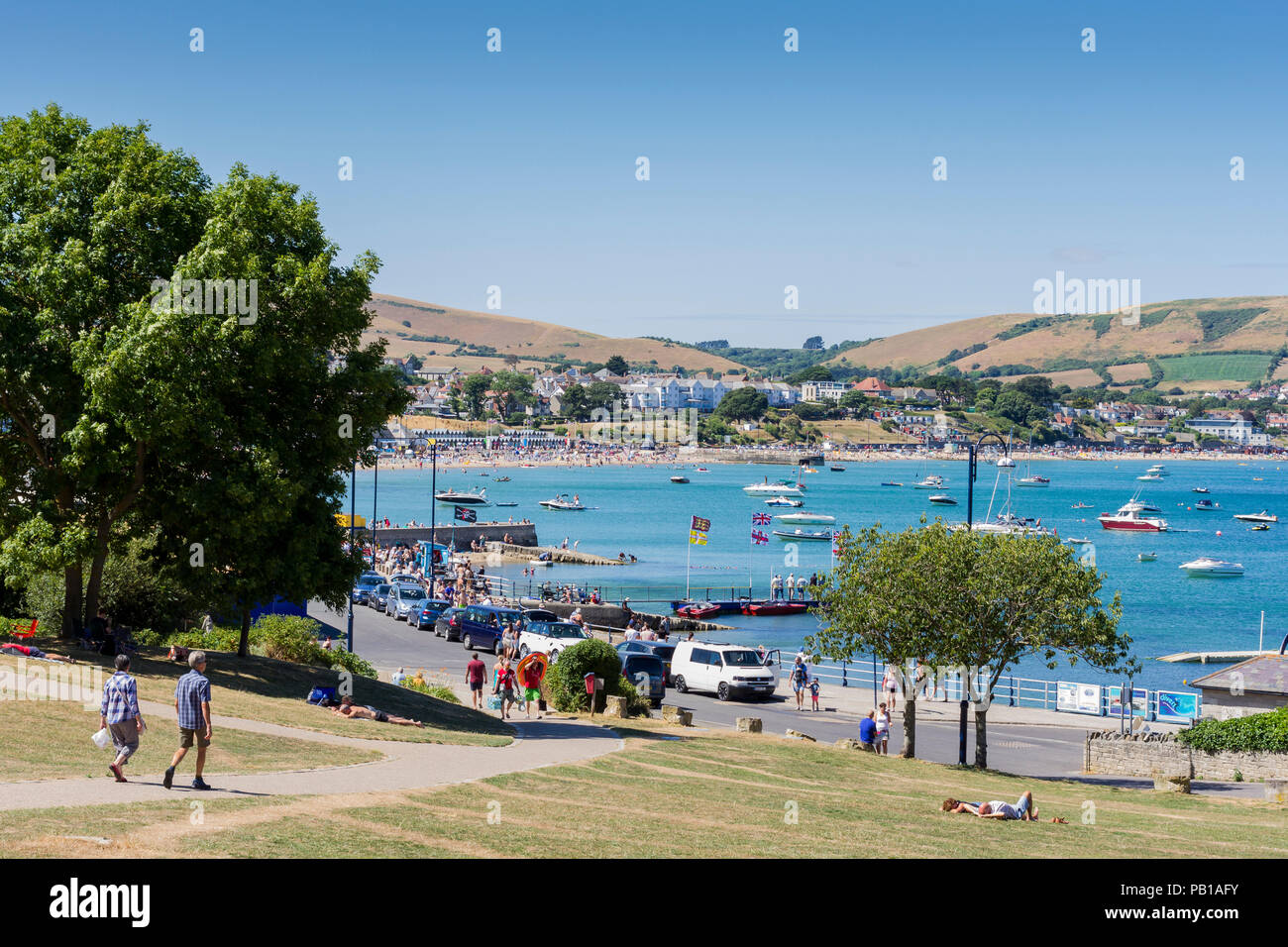 View looking down onto Swanage Bay and promenade on a busy Sunday afternoon in the summer season, Dorset, United Kingdom - Stock Image