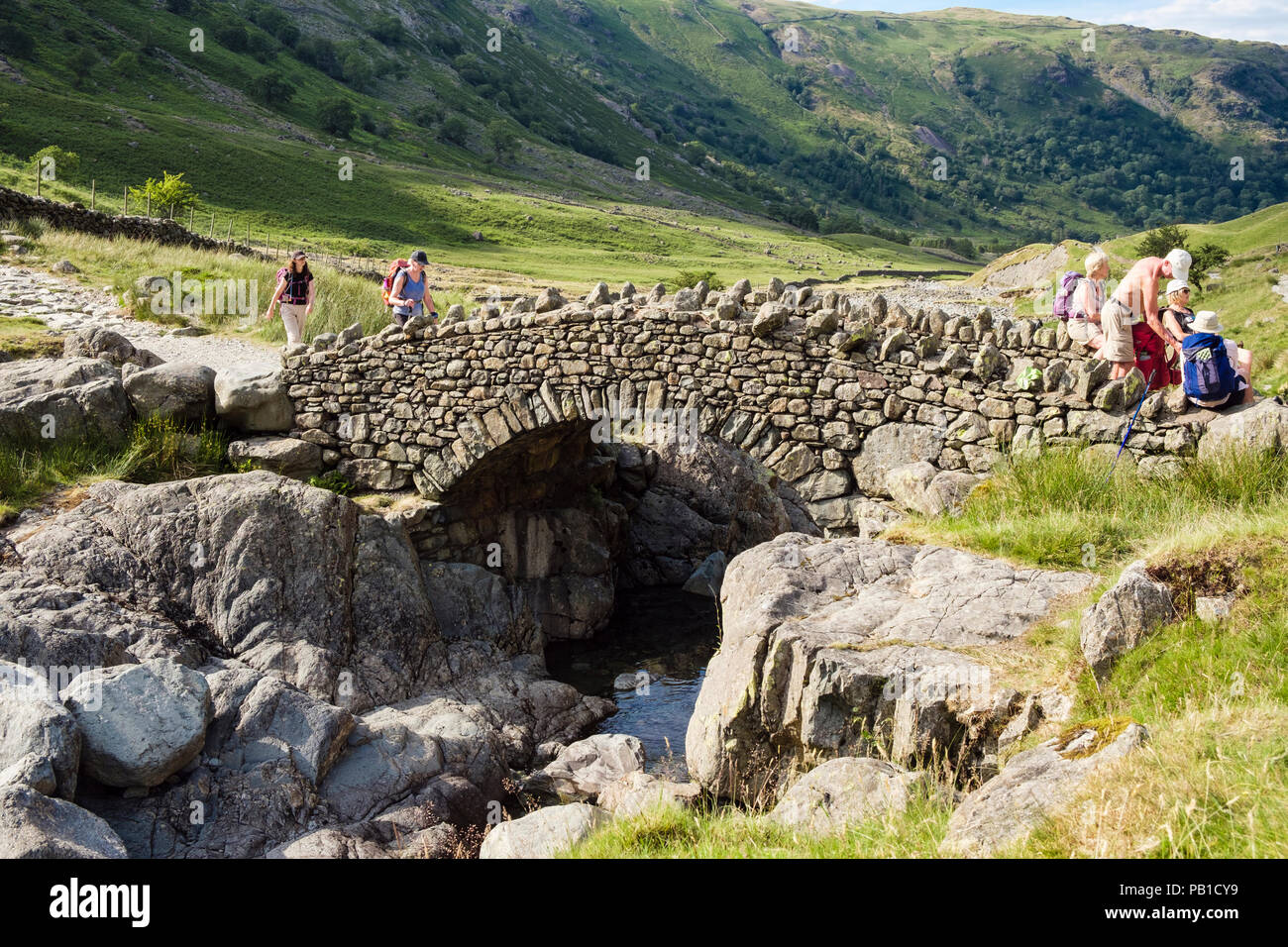 Hikers hiking on track over Stockley Bridge in Lake District National Park in summer. Seathwaite, Cumbria, England, UK, Britain - Stock Image