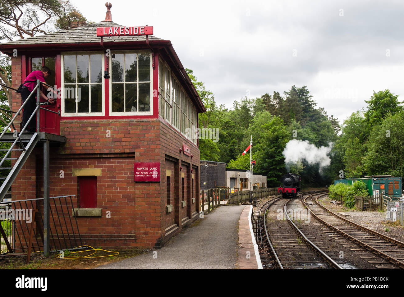 Steam train engine approaching Lakeside and Haverthwaite railway station signal box in Lake District National Park. Lakeside, Cumbria, England, UK - Stock Image
