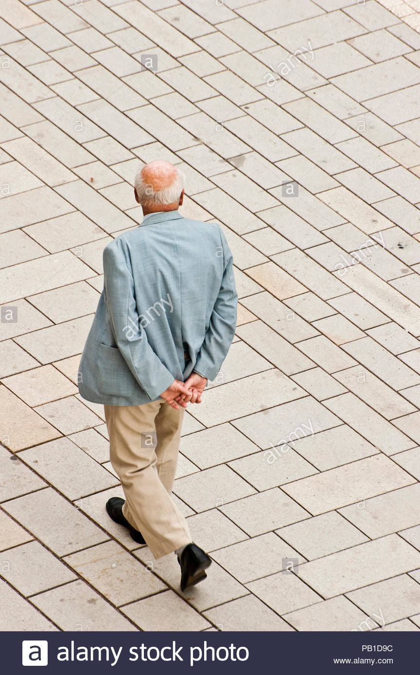 elder man wearing a suit, strolling in the street, view from above - Stock Image