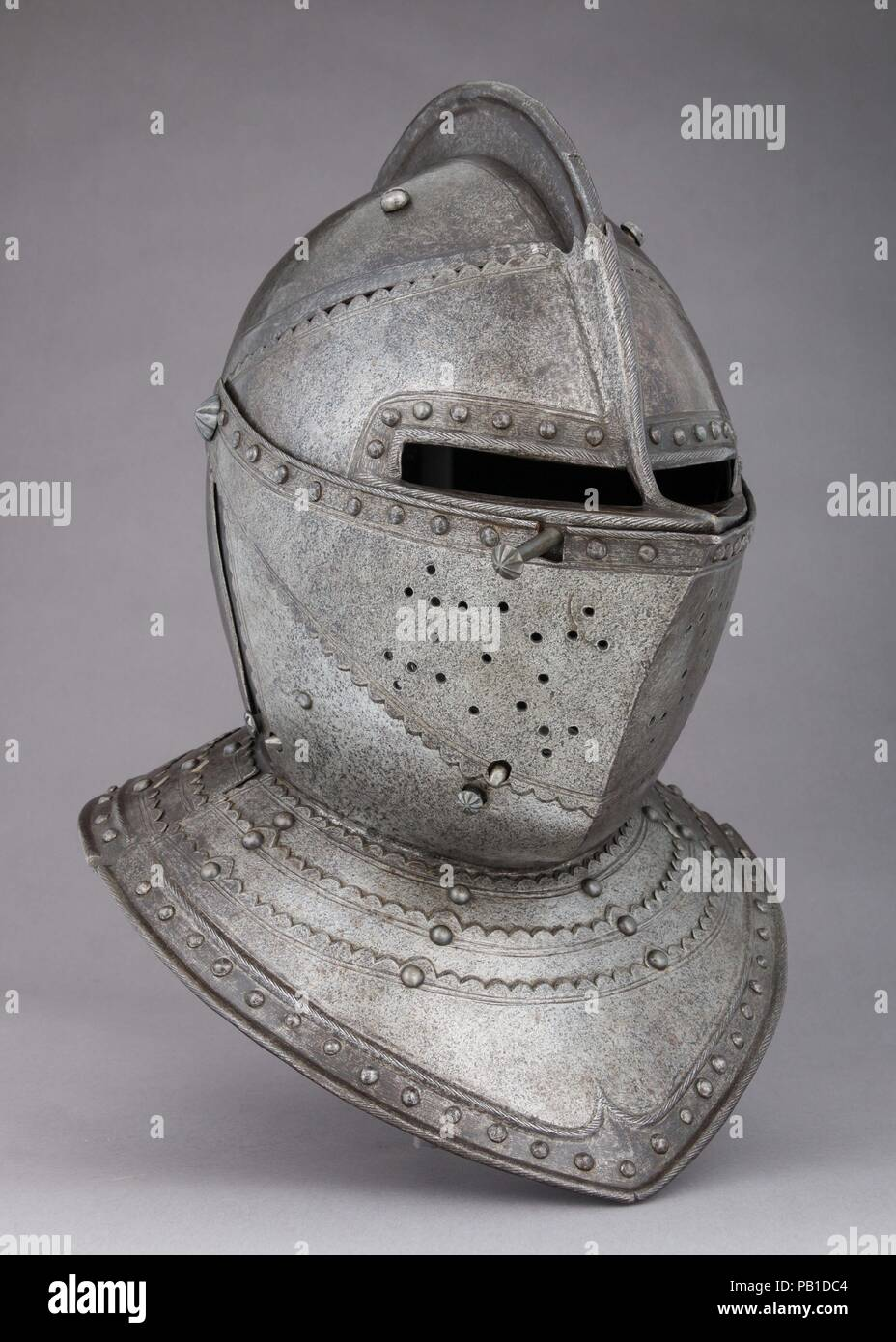 Close-Helmet for the Field. Culture: French. Dimensions: H. 15 3/4 in. (40 cm); W. 11 3/8 in. (28.9 cm); D. 14 5/8 in. (37.1 cm); Wt. 13 lb. 14 oz. (6293 g). Date: ca. 1620-30.  The two-piece construction of the helmet bowl, the scalloped edges of the plates, and the distinctive snub-nosed profile of the visor recall French helmets of about 1620-30. The reinforcing shot-proof plates screwed to either side of the bowl, which add 3 pounds 10 ounces (1675 g) to the overall weight, are rare on close-hlemets for cuirassiers. Beneath the reinforces, the original smooth blue-black surface of the bowl Stock Photo