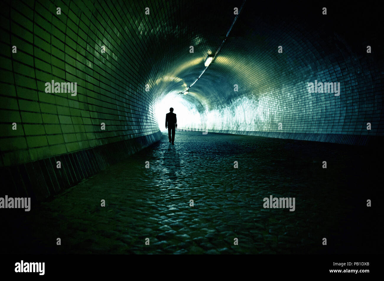 man walking under a tunnel toward the exit - image for book cover Stock Photo
