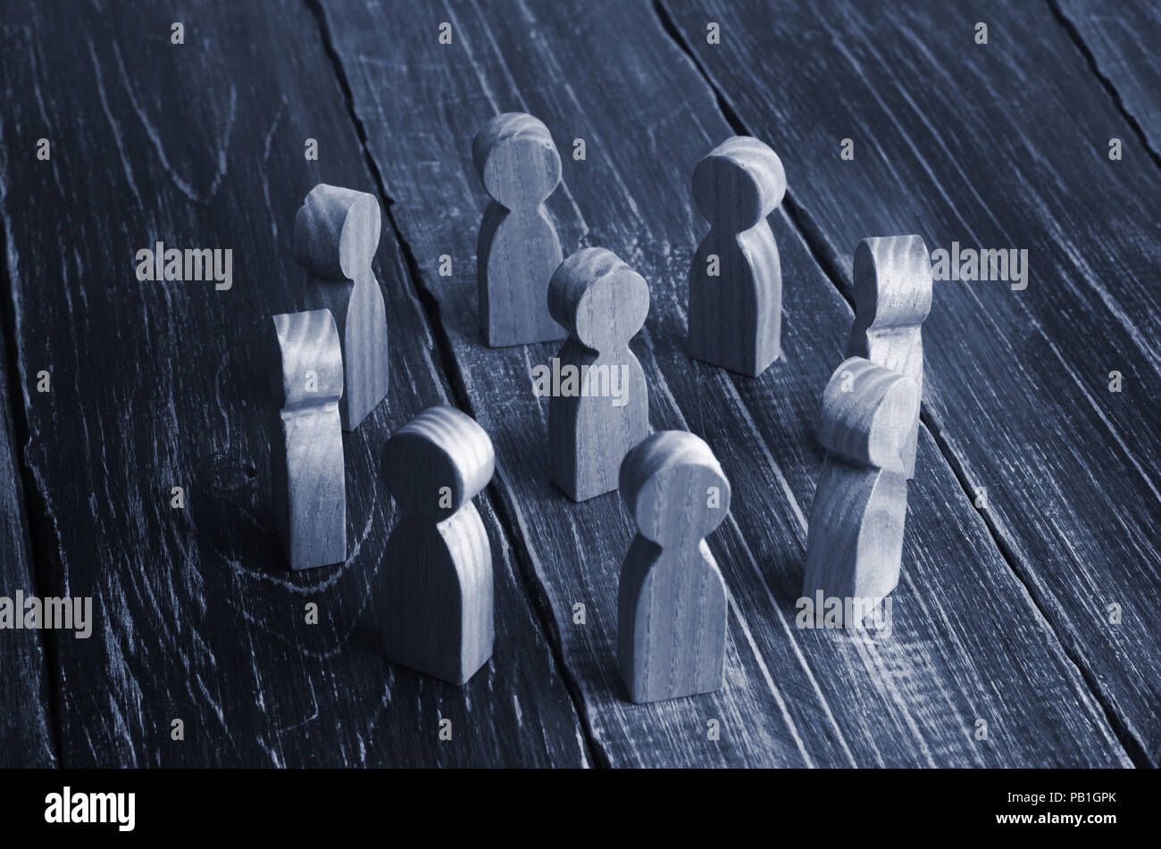 Wooden curly people stand in a circle around the person on a dark background. The concept of communication, teamwork, hierarchy and authoritarianism.  Stock Photo