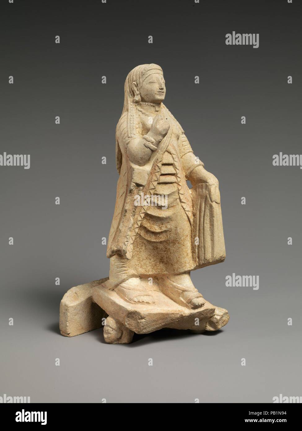 Limestone figure of a woman. Culture: Cypriot. Dimensions: Overall: 9 13/16 x 5 x 4 1/4 in. (25 cm)  Other (without base): 8in. (20.3cm). Date: late 6th century B.C..  The figure is elaborately dressed in a chiton (long undergarment), a himation (overgarment), sandals, a diadem, necklaces, earrings, and spiral bracelets with snake terminals. With her left hand she holds both her drapery and the handle of a mirror. She stands on a ledge that abutted on something else in back and that is supported by figures, of which two heads remain. This work figured prominently during the 1880s, which contro - Stock Image
