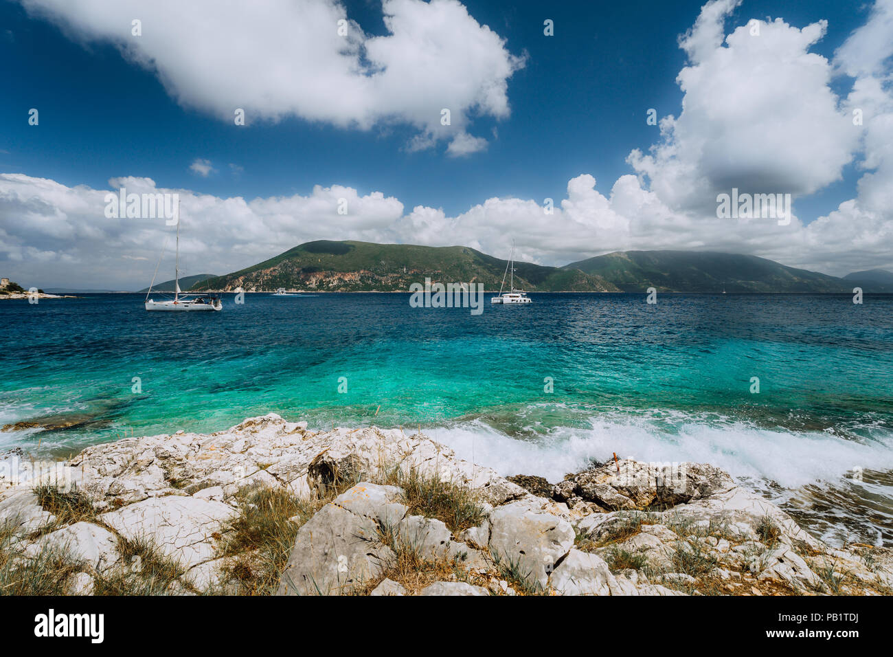 Crystal clear transparent blue turquoise teal Mediterranean sea water in Fiskardo town. White yacht in open sea at anchor under amazing white clouds, Kefalonia, Ionian islands, Greece - Stock Image