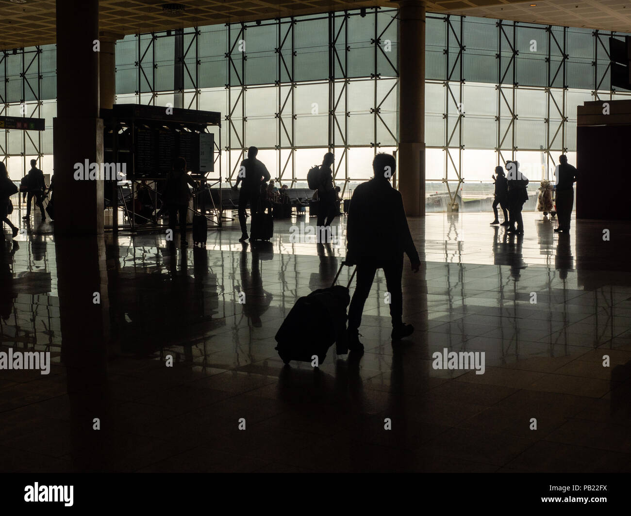 Silhouettes of travelers walking through airline terminal, Barcelona International Airport, Spain. - Stock Image