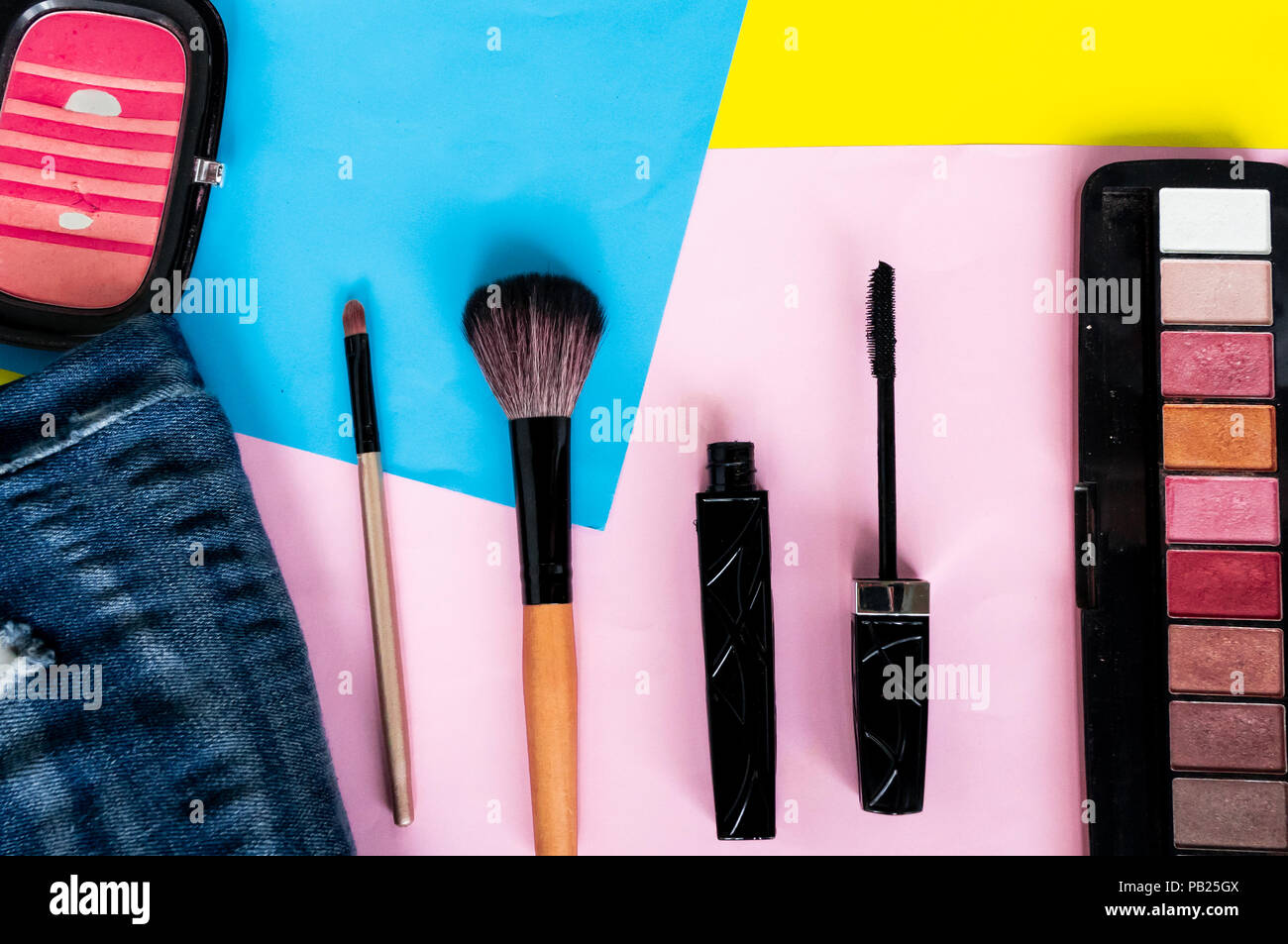 top view flat layer beauty make up set, mascara, brushes, eye shadow palate, and brush on, on two tone background - Stock Image