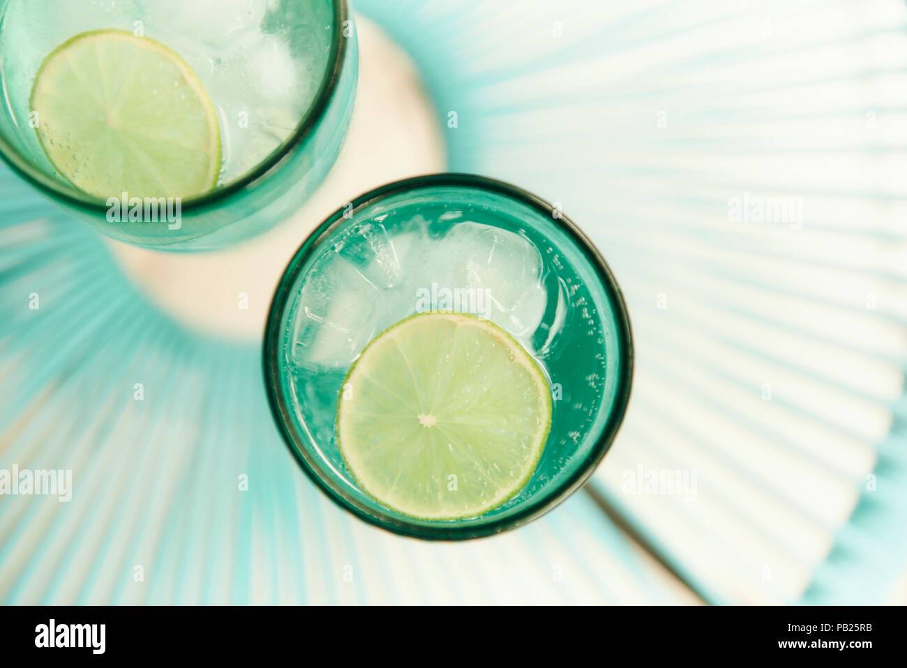 A couple of refreshing fizzy drinks with lime slices in summer. - Stock Image