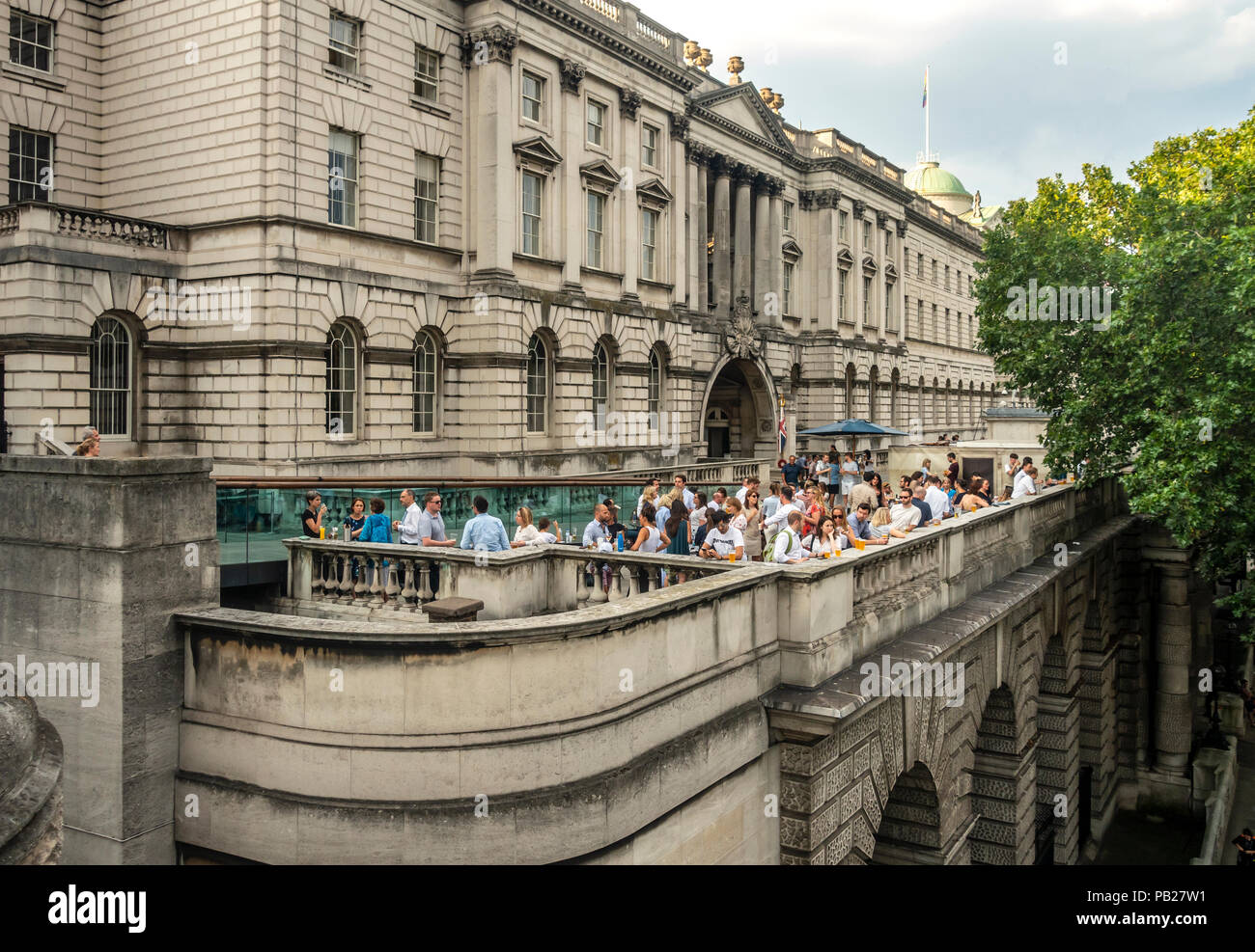 A function wit people relaxing and having a drink on the busy terrace outside Somerset House, a Grade 1 Listed Building in London, England, UK. Stock Photo