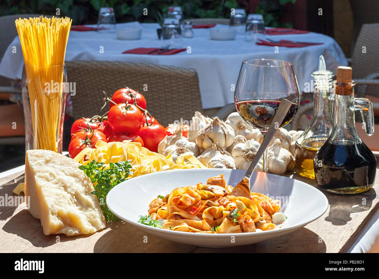 sunlit plate of Italian pasta with basic ingredients around - Stock Image