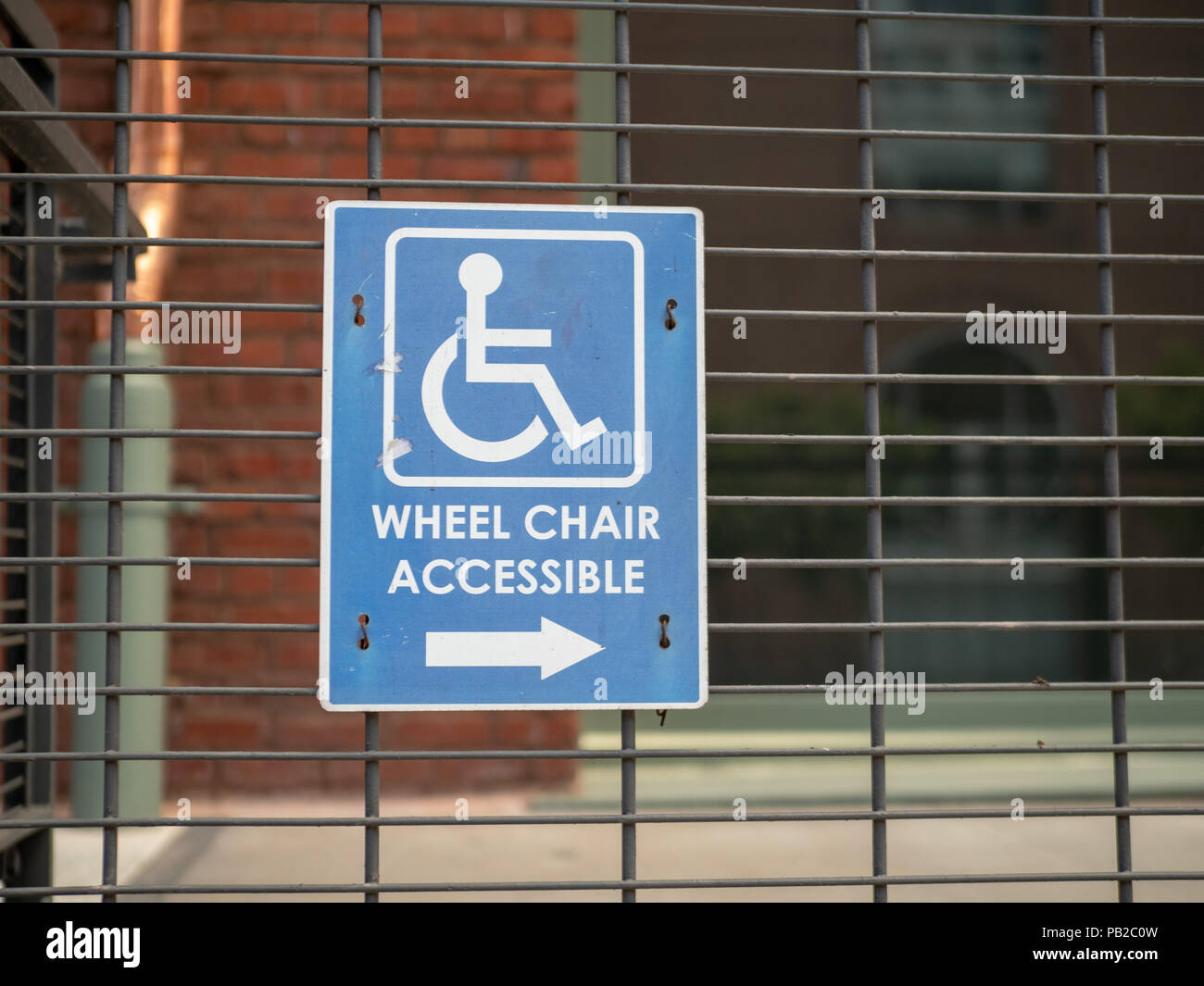 Wheel chair accessible sign pointing to the right outdoors positioned outdoors on wire railing - Stock Image