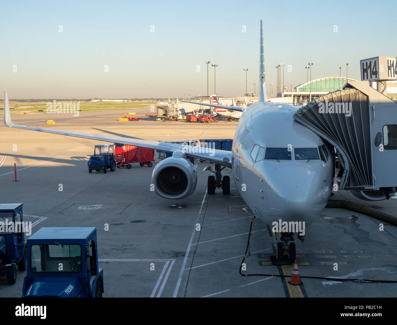 Airliner docked at airport terminal, refueling and letting passengers disembark - Stock Image
