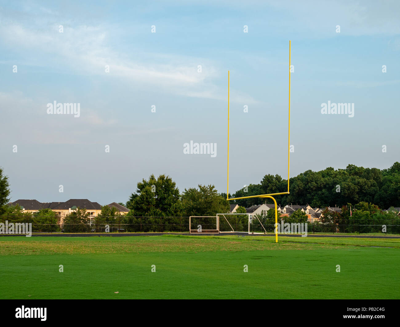 Football goal post at a high school field in the evening sun  - Stock Image