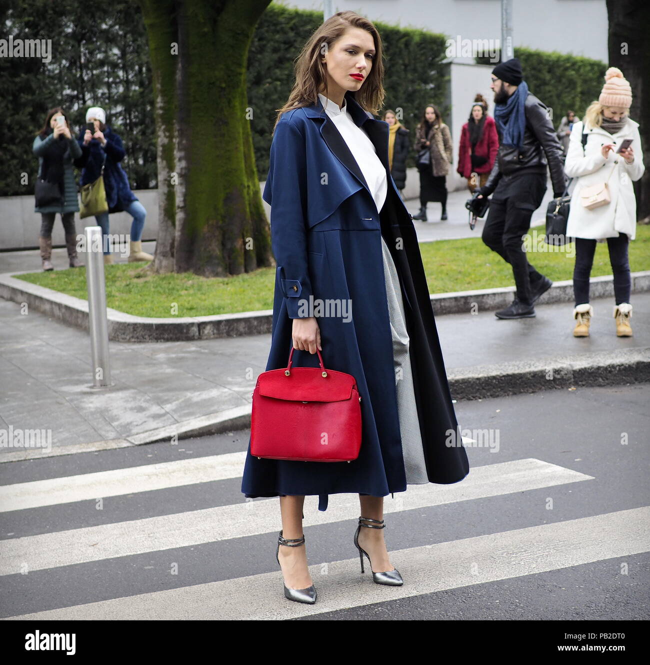 MILAN - FEBRUARY 25, 2018: Fashion blogger posing for photographers in the street before ARMANI fashion show - Stock Image