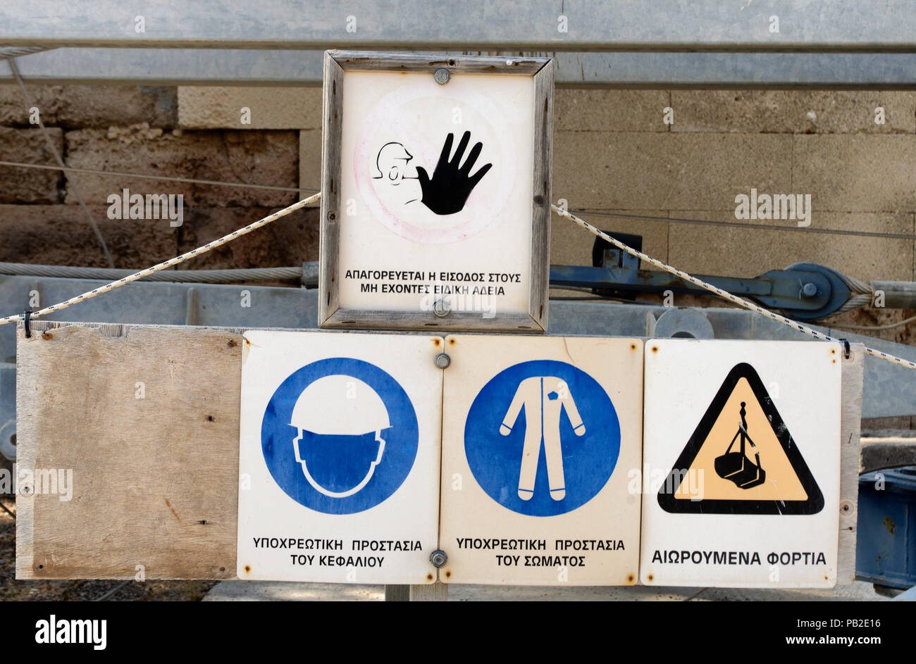 Construction safety signs with inscriptions in the Greek language ('Forbidden to enter without special permission, 'Mandatory head protection', 'Manda - Stock Image