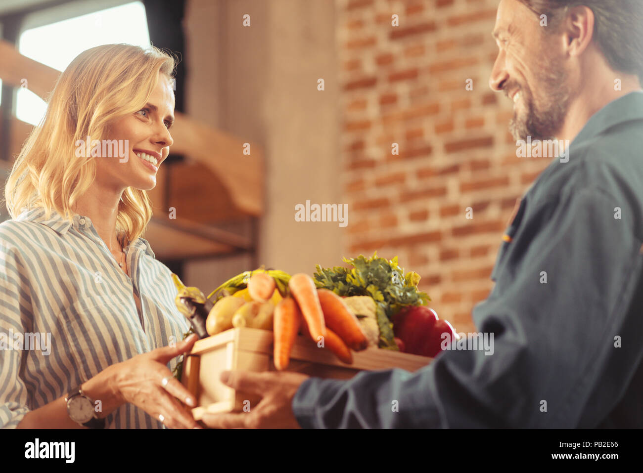 Satisfied client smiling to deliveryman - Stock Image