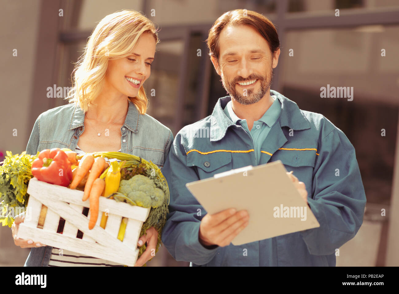 Smiling deliveryman standing near his client - Stock Image