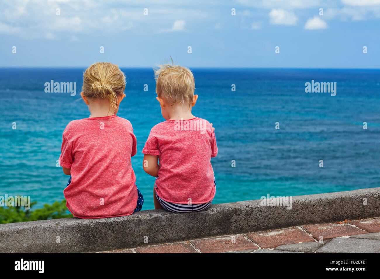 Happy kids have fun on beach walk. Couple of children sit on cliff top, talk, look at sea surf and blue sky. Travel lifestyle, outdoor activities in f - Stock Image