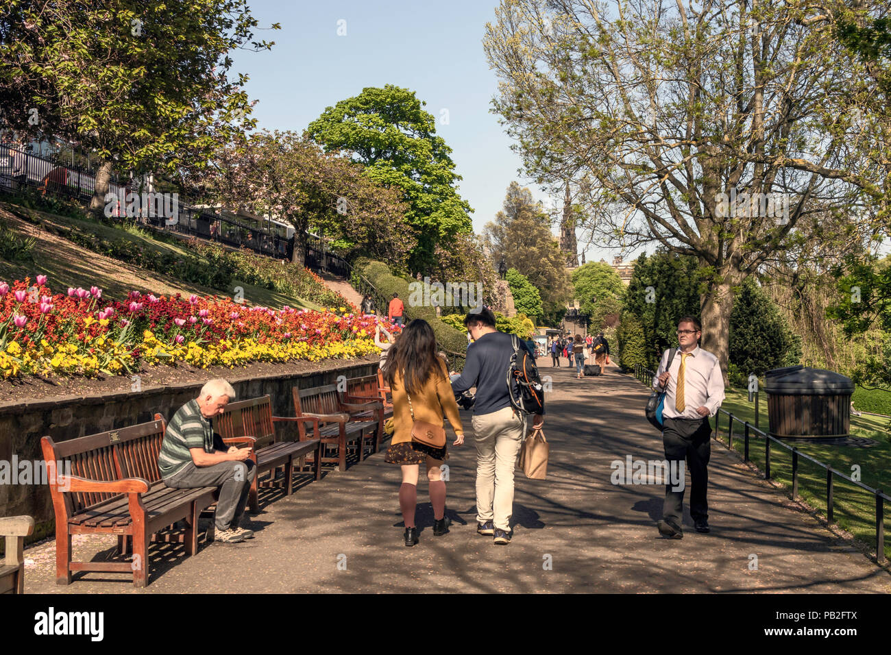 People sitting and walking through Princes Street gardens enjoying ...
