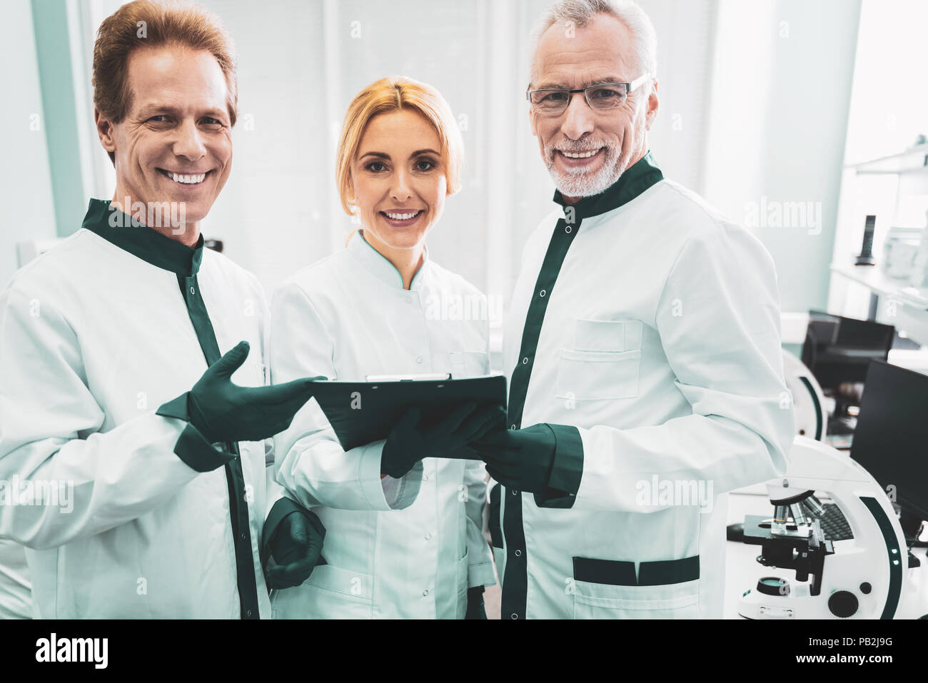 Female engineer joining company of two male workers - Stock Image