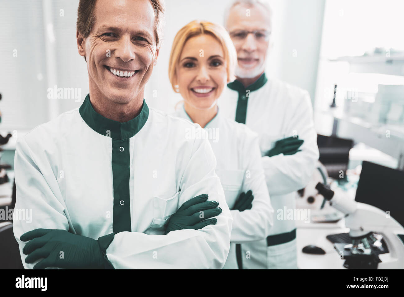 Professional chemists smiling while achieving great results - Stock Image