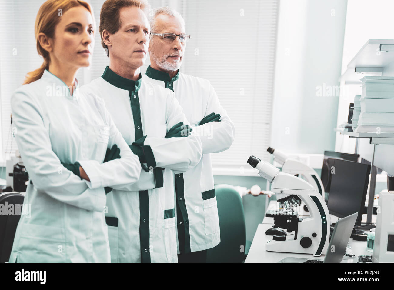 Three chemical researchers standing near modern microscope - Stock Image