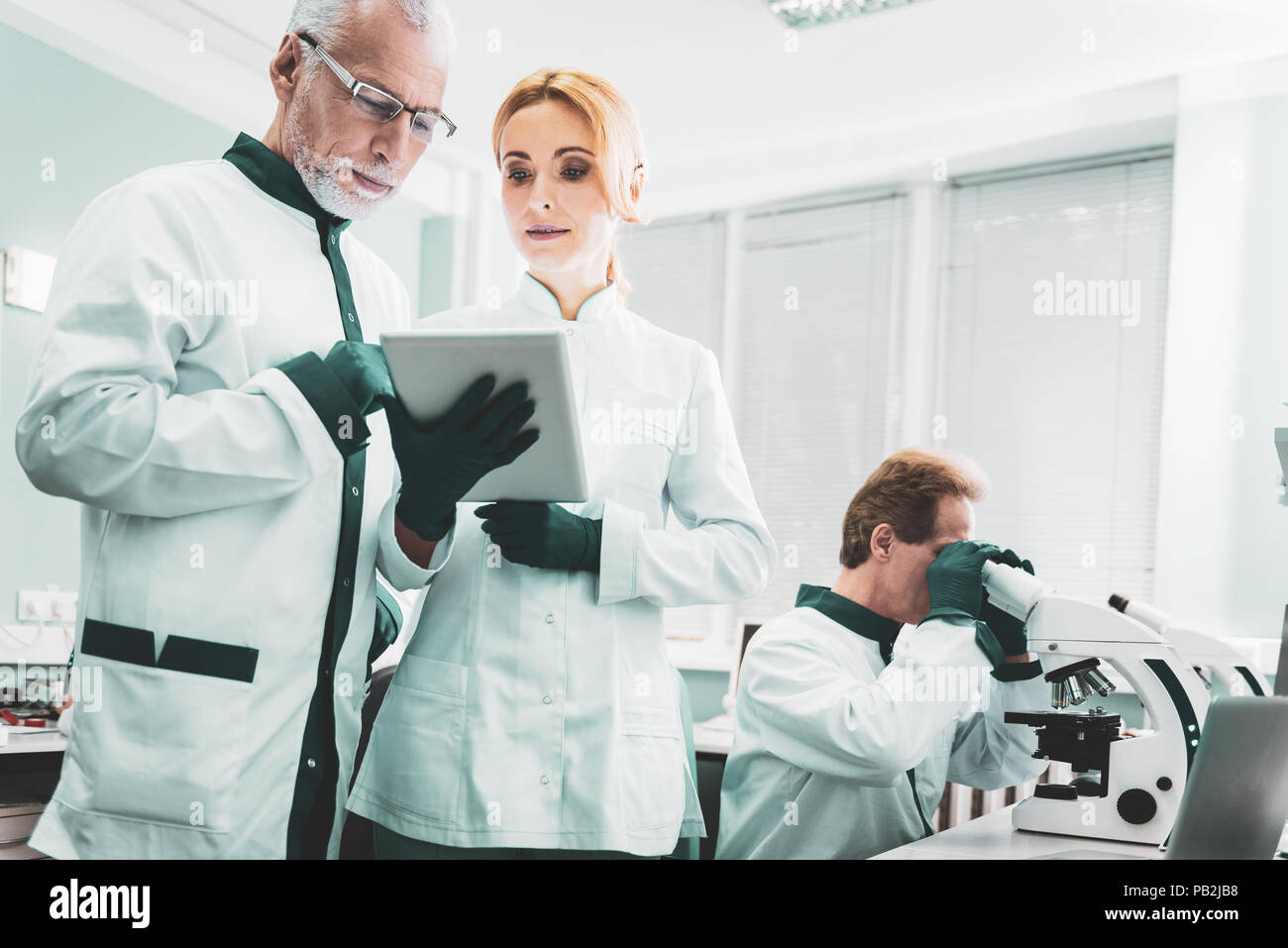 Two chemists standing near researcher using microscope - Stock Image