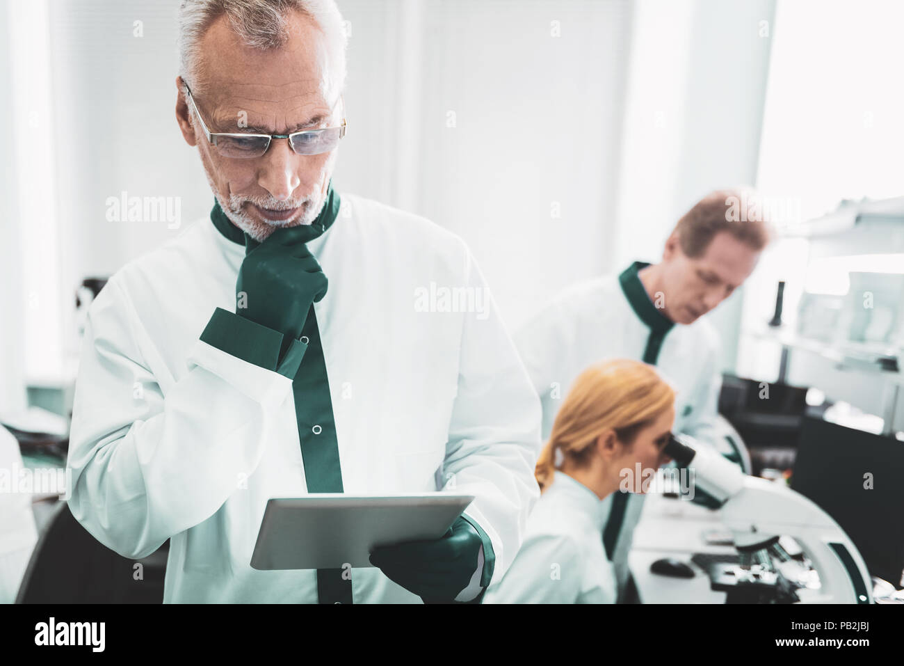 Chemist wearing glasses feeling thoughtful at work - Stock Image