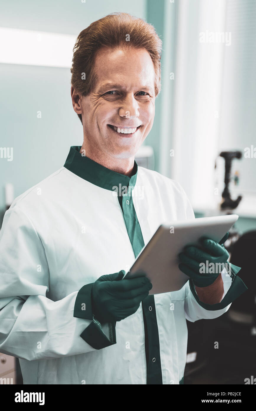 Scientist wearing white labcoat smiling standing in laboratory - Stock Image