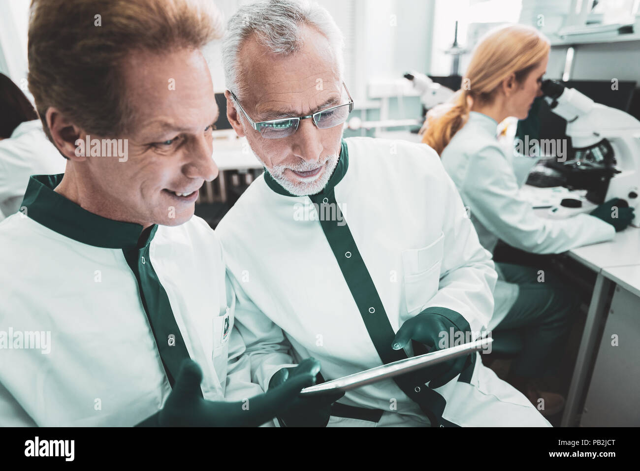 Two male biologists standing near woman in uniform - Stock Image