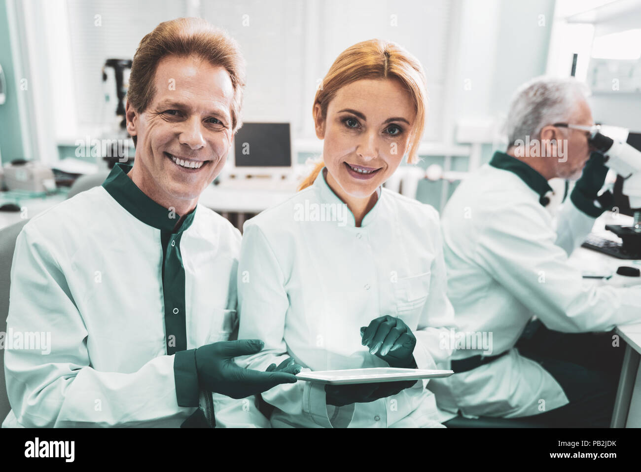 Married chemists enjoying working together in laboratory - Stock Image