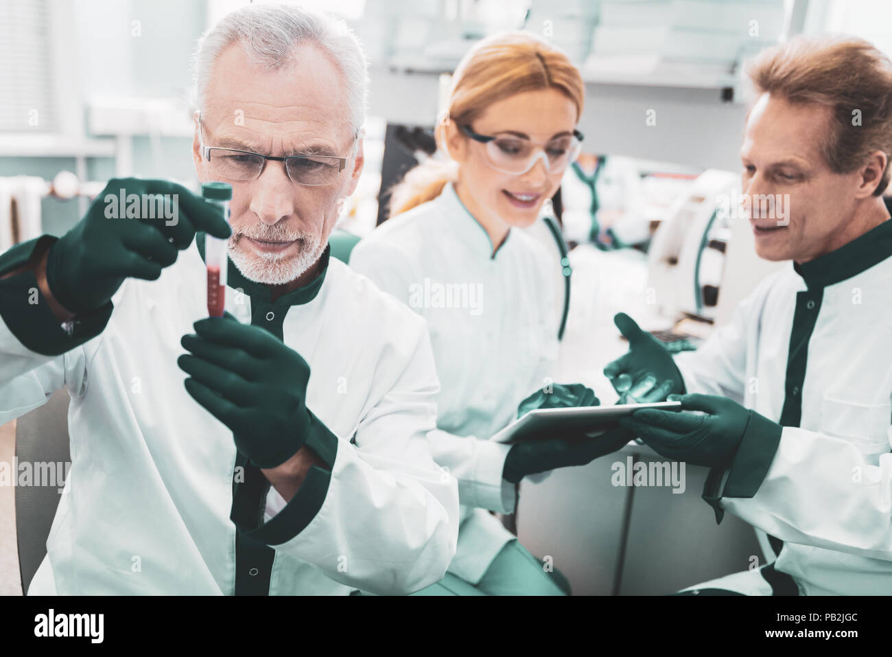 Three scientific researchers in green gloves - Stock Image
