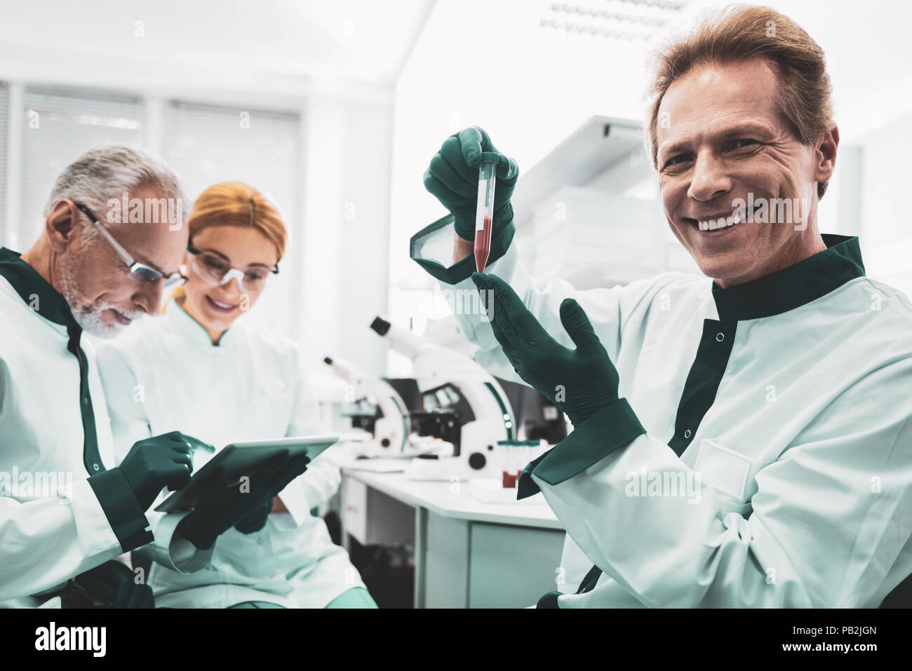 Elderly biologist smiling after making important research - Stock Image