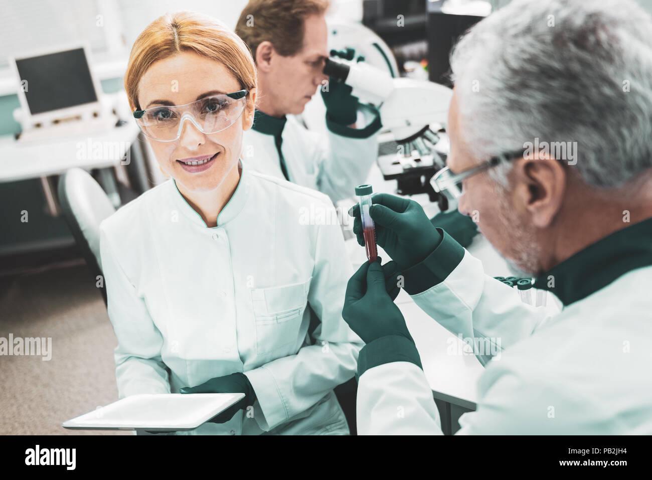 Pleasant chemist worker sitting near her director - Stock Image