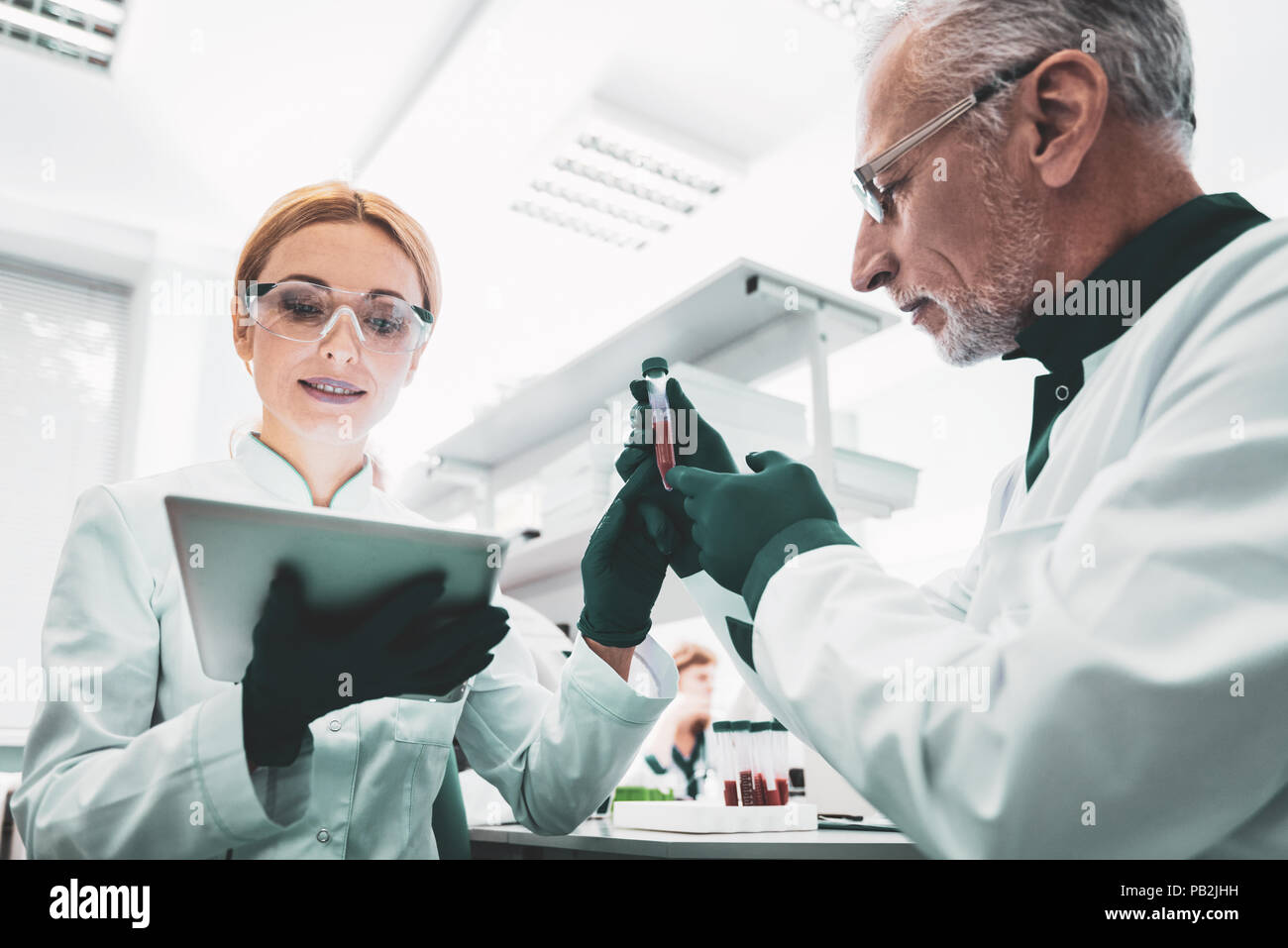 Young biologist using modern technologies during working - Stock Image