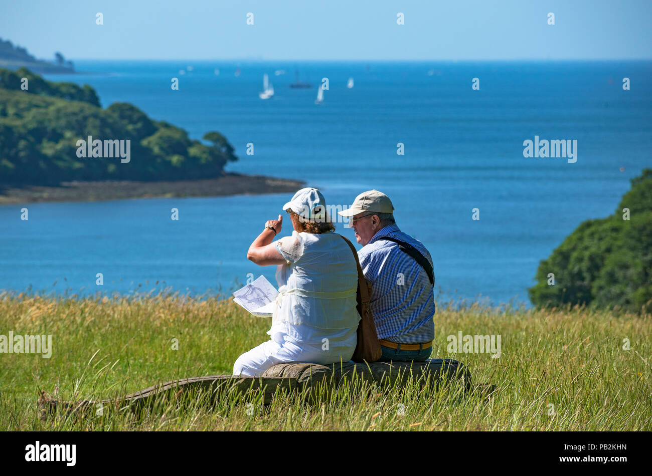 senior couple resting overlooking falmouth bay in cornwall, england, britain, uk. - Stock Image