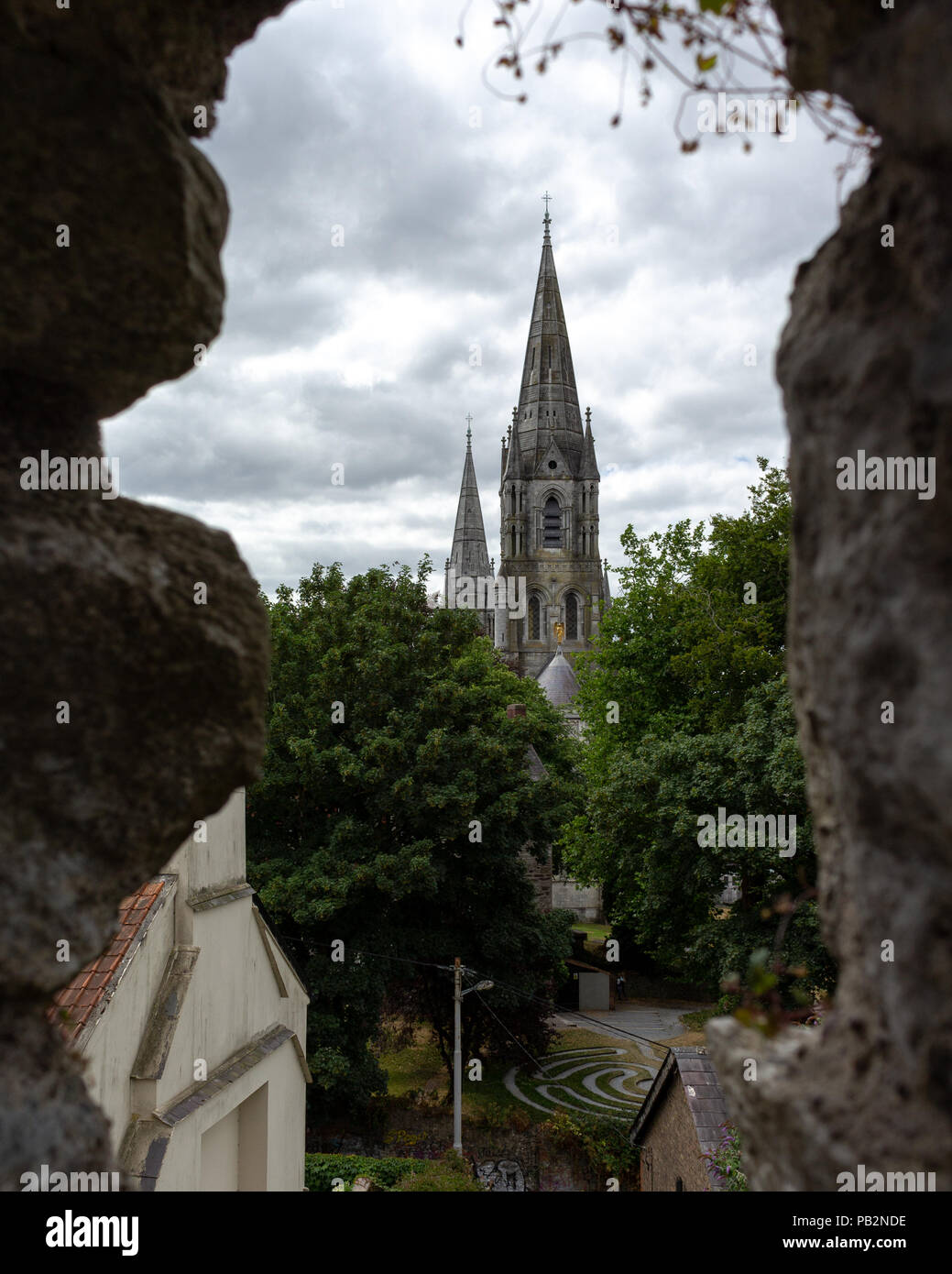 St Finbarres Cathedral seen through the wall of Elizabeth Fort. - Stock Image