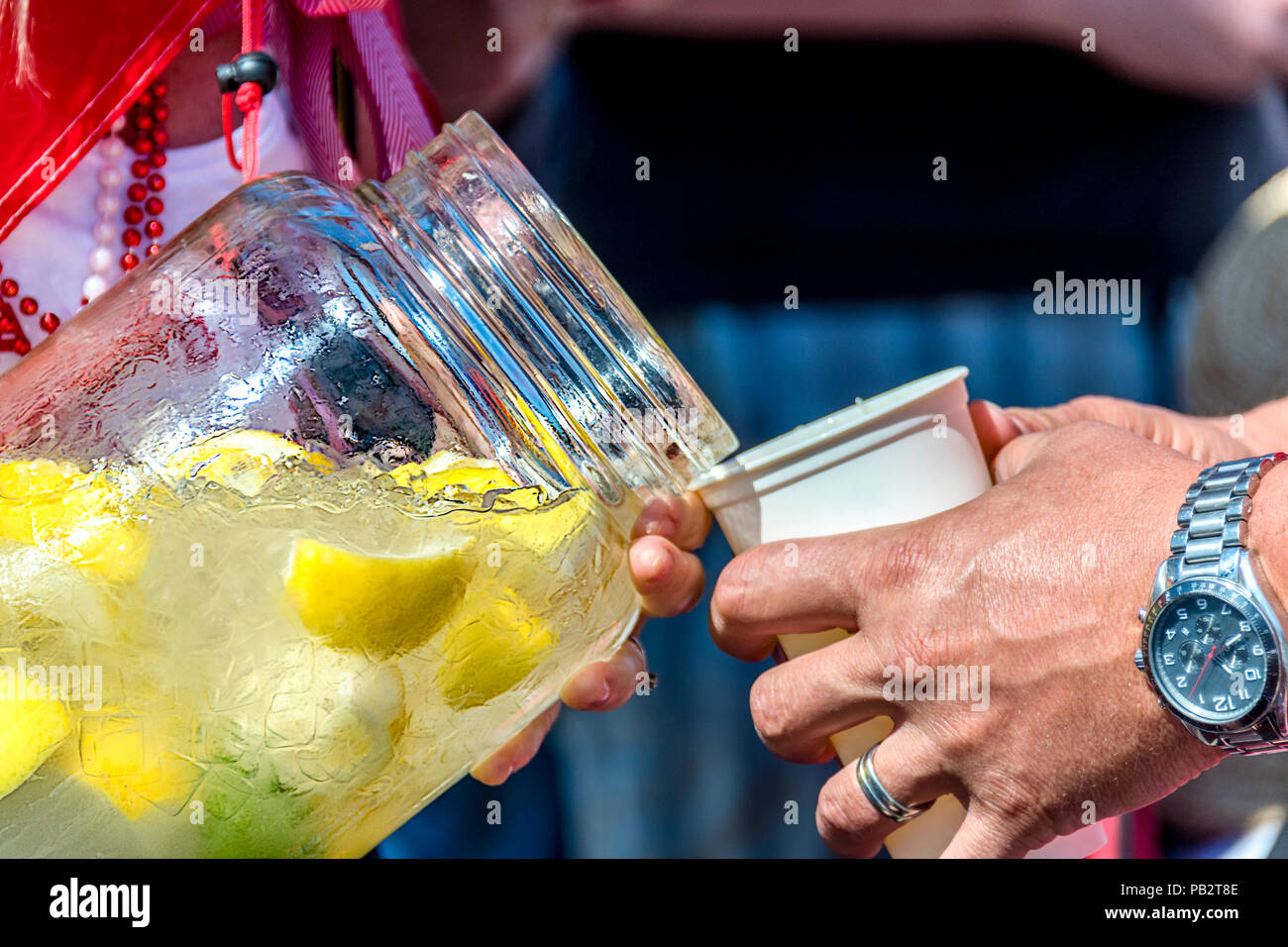Woman in beads pours cold water with ice and carved lemons from a glass bottle into a glass for man with a ring and a clock on his hand - Stock Image