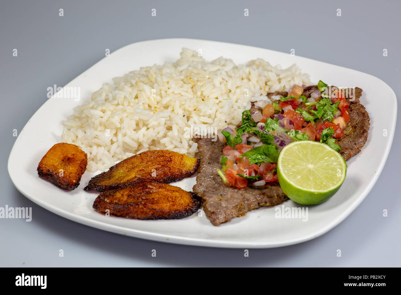A steak covered in pico de gallo surrounded by plantains and white rice on a white plate. Cuban food. Stock Photo