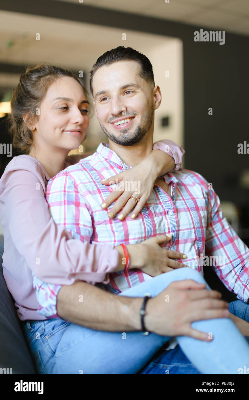 Young girl hugging boyfriend at home and smiling. - Stock Image