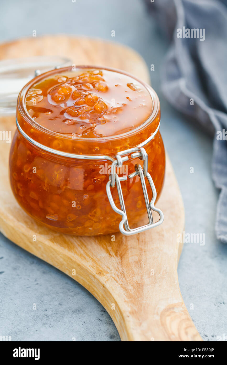 Glass jar with cloudberry jam. Nordic cuisine. - Stock Image
