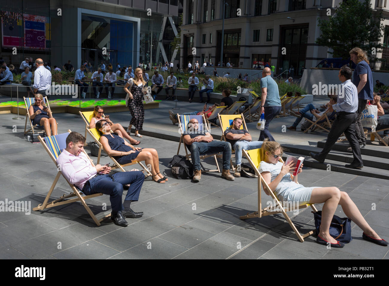 Office workers enjoy a lunchtime in Leadenhall during the 2018 heatwave in the City of London, the capital's financial district, on 24th July 2018, in London, England. - Stock Image