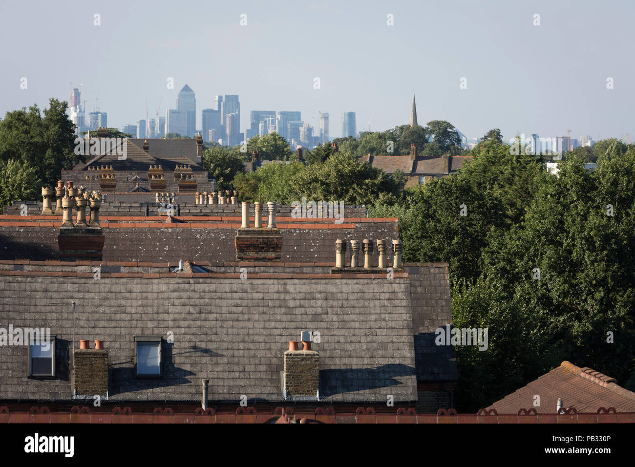 The rooftops of Sydenham houses and in the distance, the tall buildings of London Docklands, on 23rd July 2018, in London, England. - Stock Image