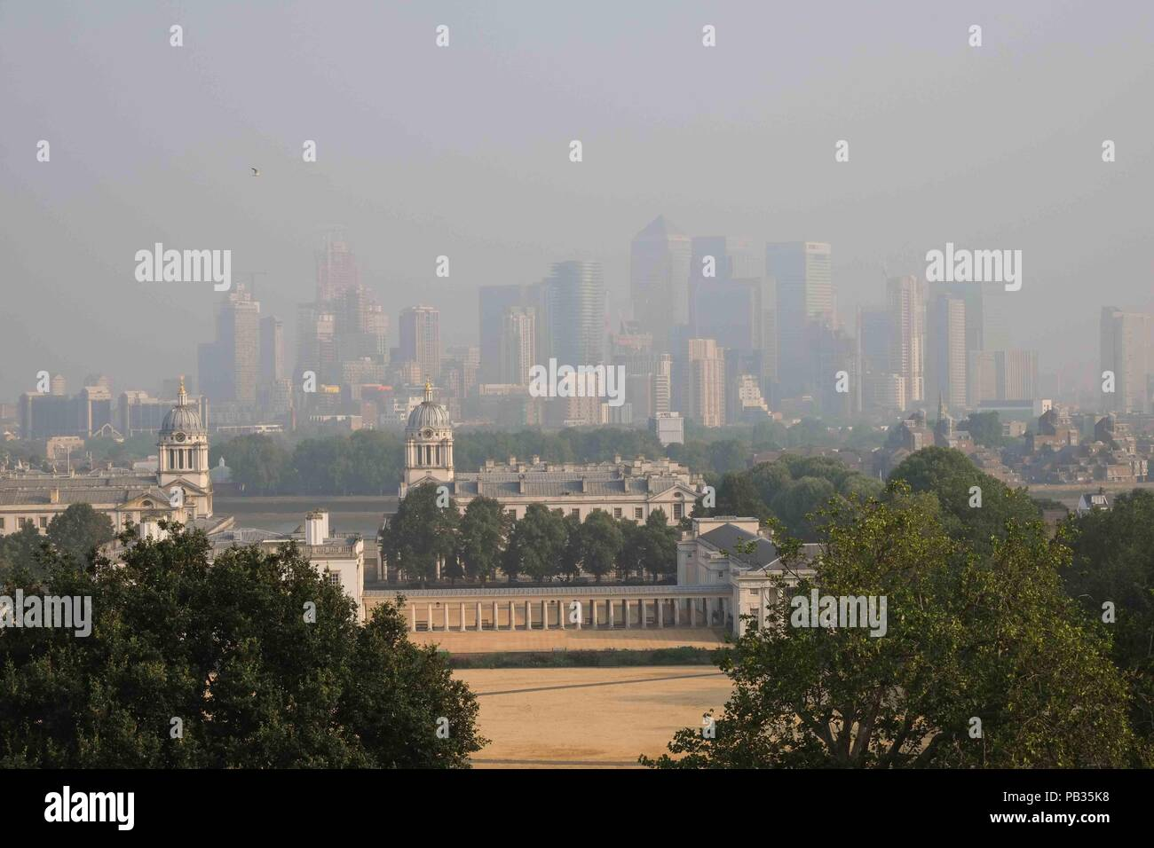 London 26th July 2018:  Early morning smog hangs over Canary Wharf, seen from Greenwich Park  as Mayor Sadiq Khan triggers a high pollution alert for London amid concerns over extremeley high tempertures. The capital is expected to reach a temperture of 36C today. Credit : Claire Doherty/Alamy Live News - Stock Image